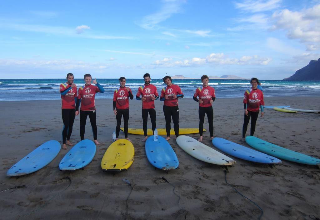 Elever med surfebrett på stranda.