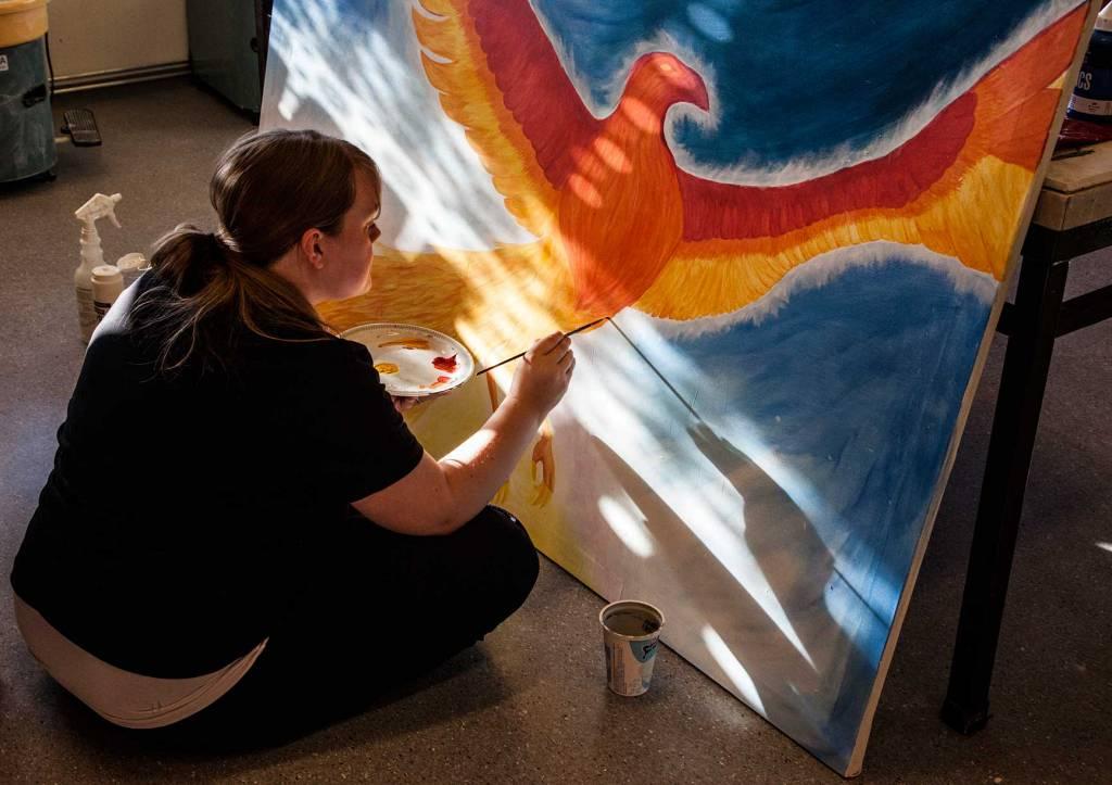 Kunstnerisk elev på linja som maler en Føniks.