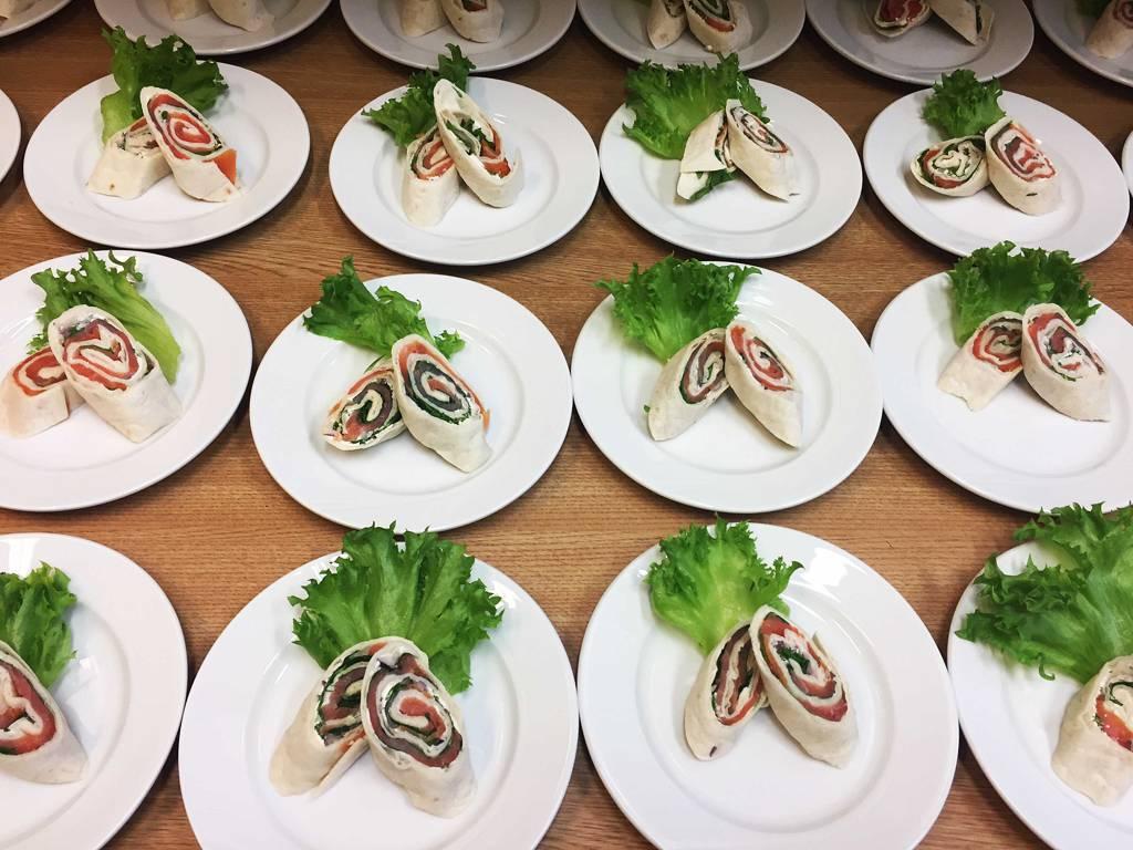 Lakseruller pent dandert på tallerkener av elever.