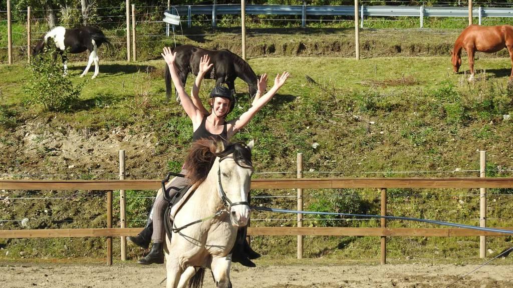 To elever øver voltige på hesteryggen.