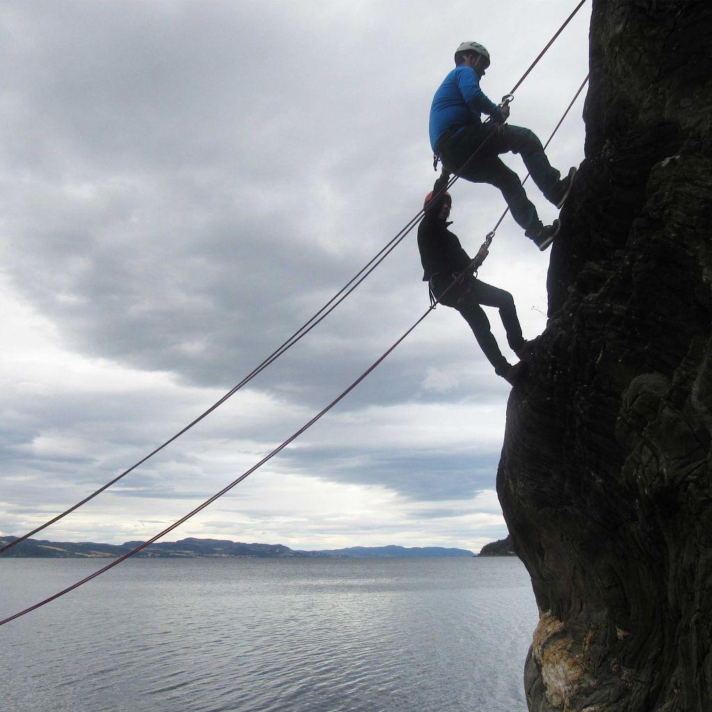 Folkehøgskoleelever som rappellerer ned et fjell.